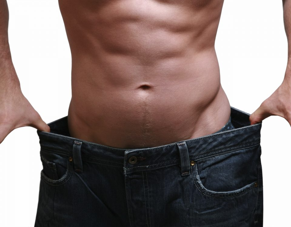 A shirtless man holding out pants that are too big, demonstrating weight loss.