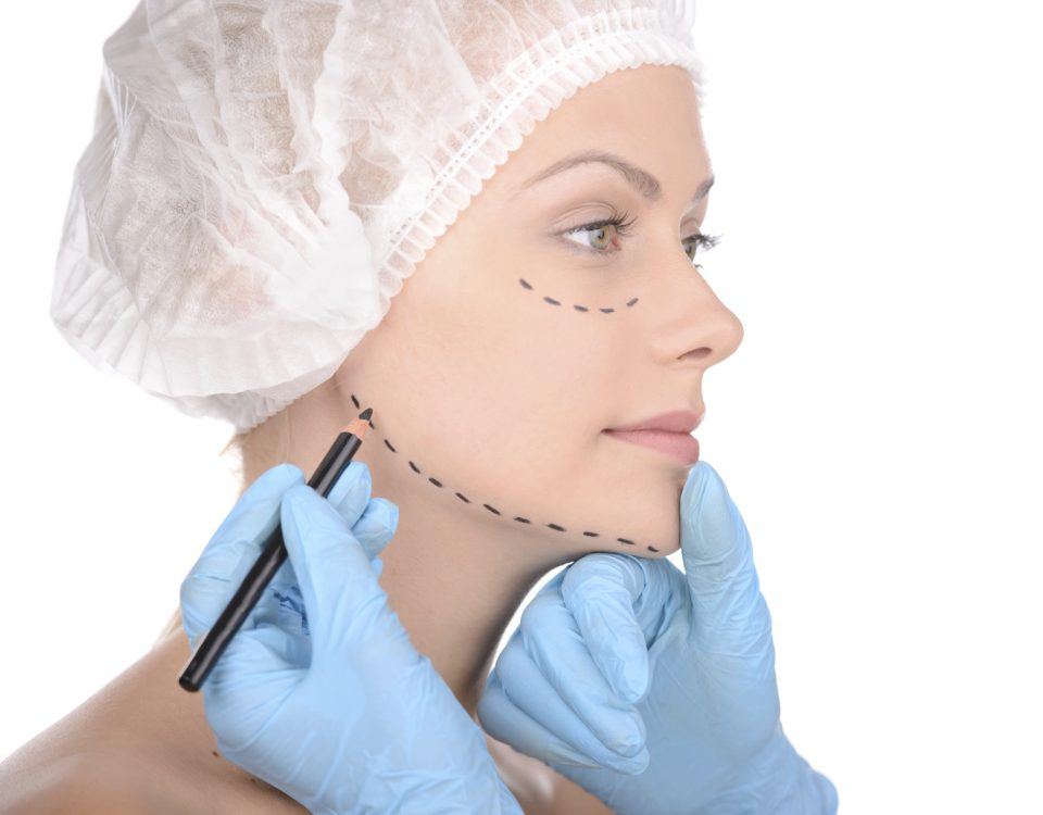 Making marks on face. Close-up of beautiful young woman in medical headwear keeping while doctors hands in gloves making marks on her face isolated on white